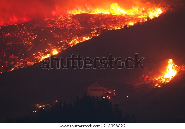 Fire fighters try to save a home from forest fire as flames rapidly approach the house.   The Carlton Complex fire - WA state's biggest wild fire in history.  100's evacuated and dozens of homes lost