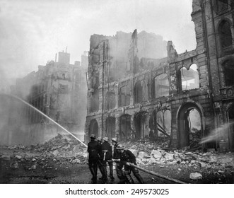 Fire fighting during WW2 Battle of Britain. Firemen at work in bomb-damaged street in London, after Saturday night raid, ca. 1941.