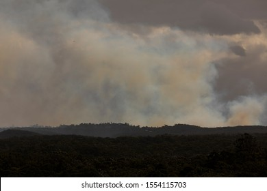 Fire fighting helicopters flying in smoke during a bush fire in The Blue Mountains in Australia