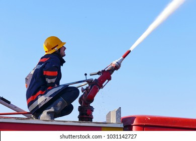 Fire fighting with water cannon / Firefighter extinguishes a fire with a cannon