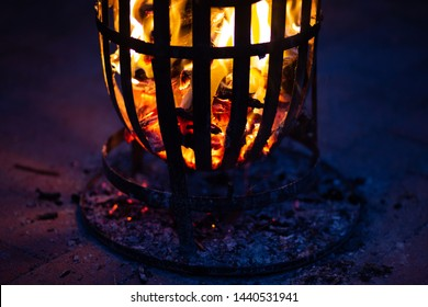 Fire in firepit on top of brick pavement. Shadows cast through the holes in the fire pit / cage. Red flames casting red shadows.