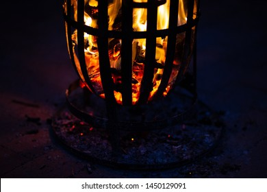 FIre in firepit on top of brick pavement. Shadows cast through the holes in the fire put / cage. Red flames casting red shadows.