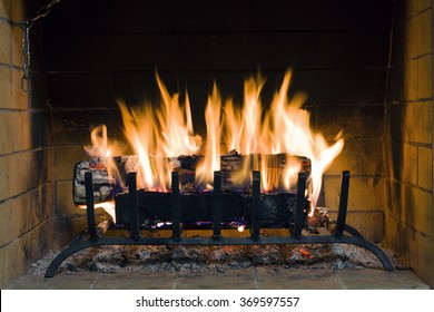 Fire in fireplace. Closeup of firewood burning in fire. Fireplace in the house. Firewood burns in a fireplace. A fireplace in a country house