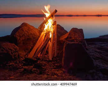 Fire and flames of atmospheric campfire on the beach at night. Still water of the lake on the backgound with warm colors of sunset. Very shallow dept of field.
