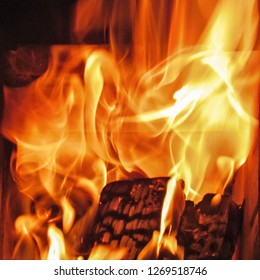 Fire flames of a burning wooden log in a fireplace. Natural bright red-yellow texture of flames movement is an expressive design element of an abstract dramatic, mystic or romantic background.