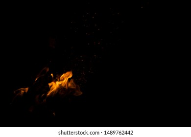 fire flames fuzzy motion  orange natural illumination in deep black darkness, cozy campfire background wallpaper pattern with empty space for copy or text