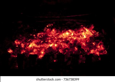 Fire flames on a black background. Red charcoal. Texture bonfire embers. Embers, smoldering coals background. Orange and red embers texture. Burning wood in the fire.