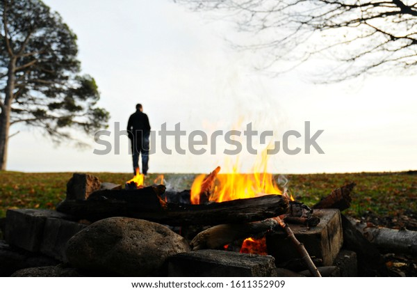 The fire in the foreground and the blurred silhouette of a man walking away out of focus