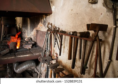 Fire in the furnace. Smithy. Blacksmith tools, traditional craft.