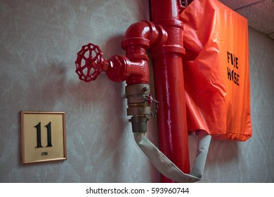 Fire hose connected to a red water pipe through a valve, hidden in a bag on 11th floor of a building