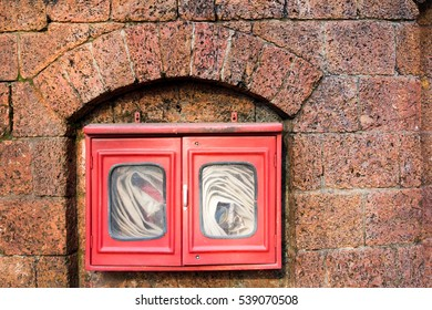 Fire hose in red box on brick wall background