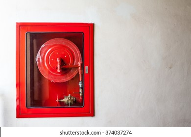 Fire hoses packed inside of red emergency box at the wall
