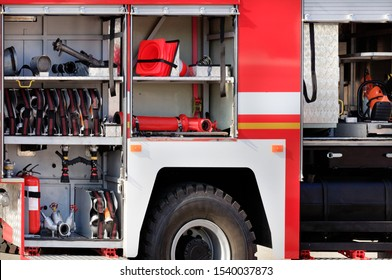 Fire hoses, valves, cranes, road cones, hydrants and manual fire extinguishers are located in the cargo compartment of an equipped fire truck, free copy space.