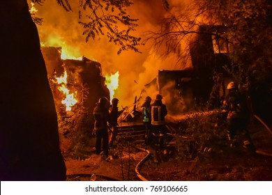 fire in the house at night. Firefighters extinguish a large-scale fire in a private house at night
