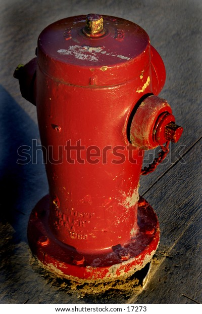 Fire hydrant isolated with pavement in the background.