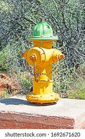 A fire hydrant painted yellow and green is mounted on a concrete platform.