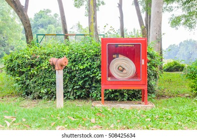 Fire hydrant and pipe roll for fire emergency in red metal boxes in garden