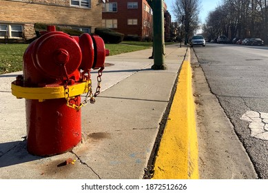 A fire hydrant in red and yellow and yellow line on a pavement along a street road where parking forbidden