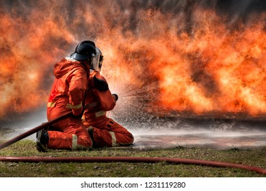 Fire men spray water to extinguish a fire, aganist huge orange flame