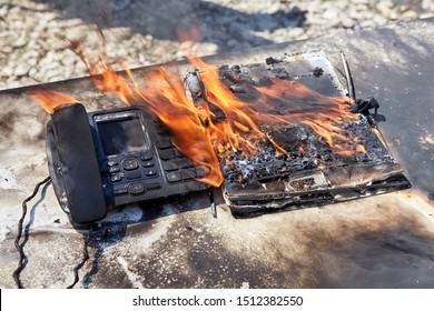 A fire in the office, a flame destroys a wired telephone and laptop, an office desk ignited. A landline telephone burns in an office fire.