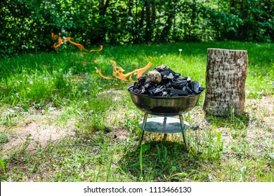 Fire on barbecue charcoal grill. Grilling food on a weber type small cheap BBQ grill at home. Family backyard barbecue - BBQ picnic