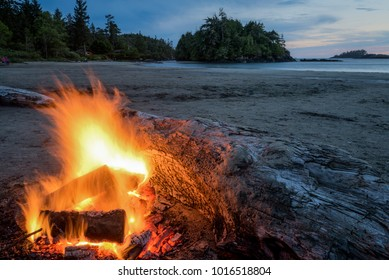 Fire on the beach behind large log at sunset