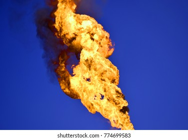 Fire on flare stack at oil and gas central processing platform while burning toxic and release over pressure from process in the blu sky back ground.