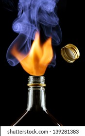 fire over the neck of a bottle of spirits, a flying bottle cap.