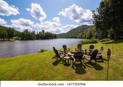 A fire pit surrounded by adirondack chairs next to the Allegheny river in Warren county, Pennsylvania, USA on a sunny, summer day