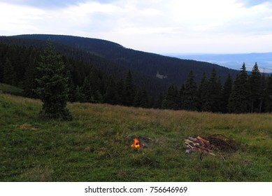 Fire place in the mountains. Bonfire in the middle of hill. Sticks and stones to burn. Nature trip landscape.