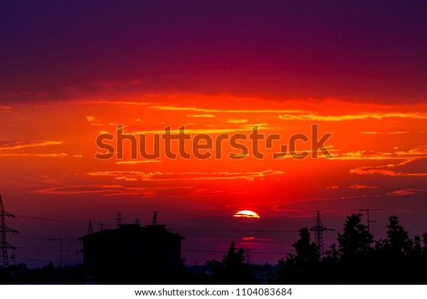 Fire red urban sunset with black silhouette of light poles and houses of cityscape. Copy space. Red sunset background.