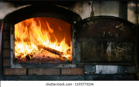 Fire roaring and burning wood in traditional masonry oven, also known as brick oven or stone oven.