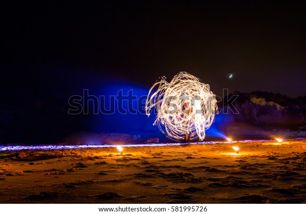 Fire show on the beach. Holiday travelers. Slow shutter speed. Night Scene, Portugal