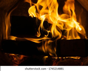 Fire in the stove. Tongues of flame. Firewood burns in the stove. Birch firewood. Open fire. Heated at home. Firewood burns in the fireplace. High temperature. Heated at home. Inside a metal furnace.