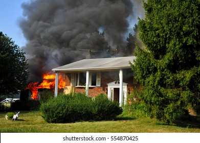 fire at suburban home with fireman in bucket appearing in smoke cloud behind house