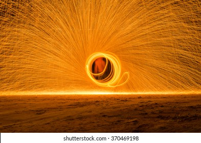 Fire swirl show on the beach during party night