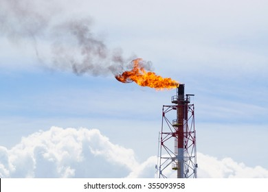 Fire torching against the sky burning gas flaring Gas or flare burn on offshore platform.