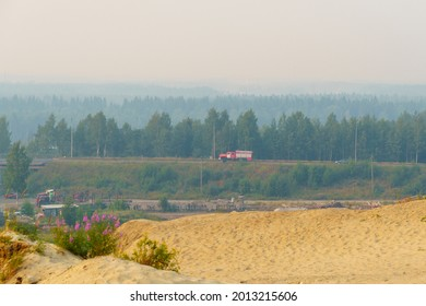 Fire truck hurries along a country road covered with smog from forest fires