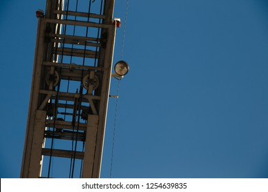 Fire truck ladder leading up into blue sky.