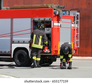 Fire trucks and firefighters with uniforms and protective helmets during an emergency