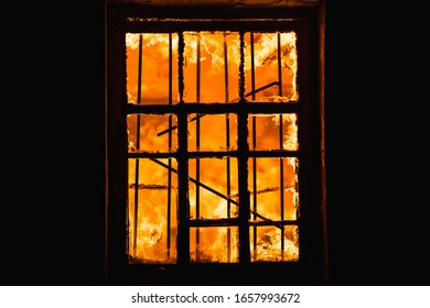 Fire in a window in a wooden house.