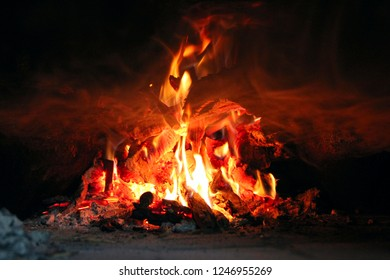 Fire wood brighly burning in furnace. Firewood burn in rural oven. Burning firewood in fireplace closeup. Fire and flames. Close up of burning fire wood in fireplace