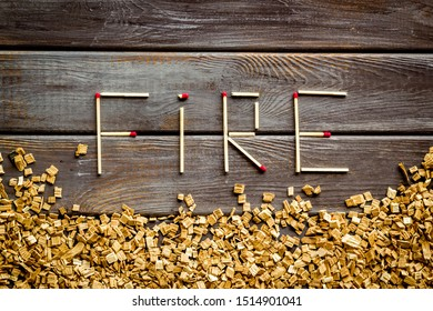 Fire in woodes concept with fire text and kindling frame on wooden background top view