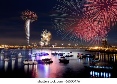Fire works firing up into the sky with a boat on a river below them, with a reflection on the water