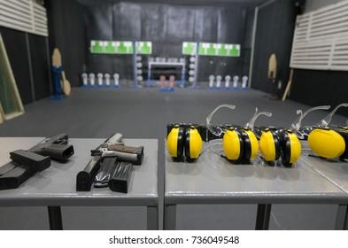 firearm, bullets, ear protection, eyeglasses at shooting range