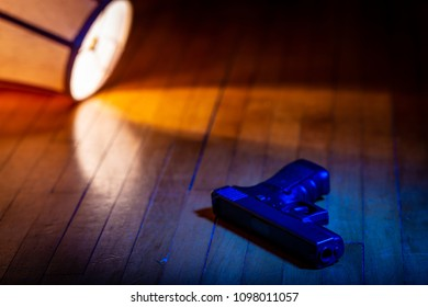 A firearm lays on the wood floor in front of a lamp which has been knocked over.