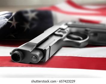 Firearm lying on American flag. Gun control concept