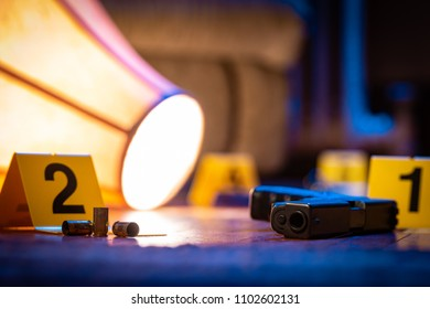 A firearm and other evidence is marked with evidence markers on the floor of a home. A knocked over lamp lays nearby.