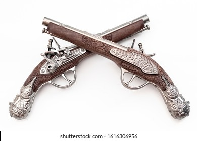 Firearms dating to the american revolution and antique collectables concept with ornate old fashioned dueling flintlock pistols crossed in duel isolated on white background with clipping path cutout