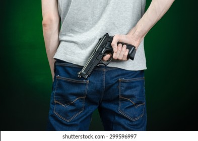 Firearms and murderer topic: man in a gray t-shirt holding a gun on a dark green background isolated in studio